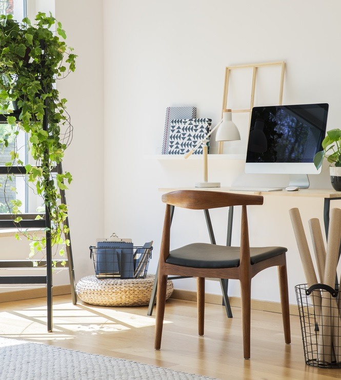 Wooden chair at desk with desktop computer in white home office interior with plant on ladder