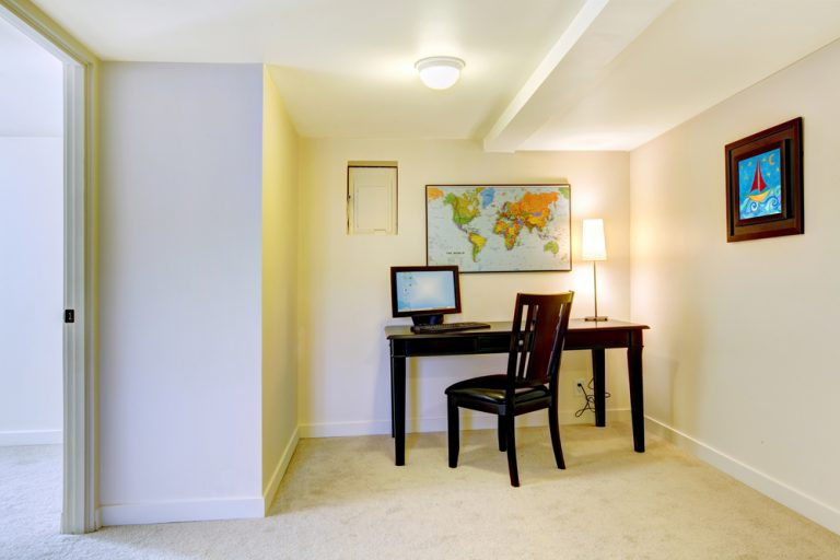 Home office desk with map on the white wall