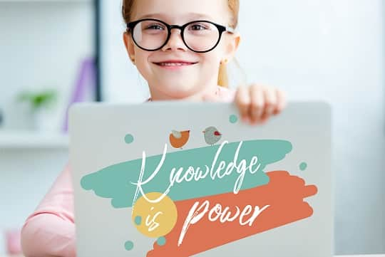 Young girl with laptop that says Knowledge Is Power