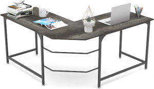 Large L-shaped desk with a laptop and plants
