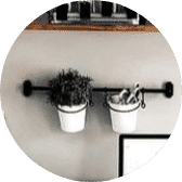 Rail with hanging pots containing a plant and stationery