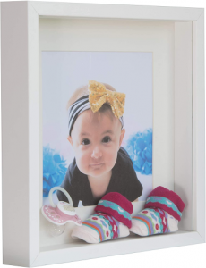 White shadow box with an image of a baby with baby shoes