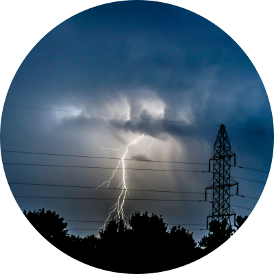 Electrical storm with a bolt of lighting striking power wires.