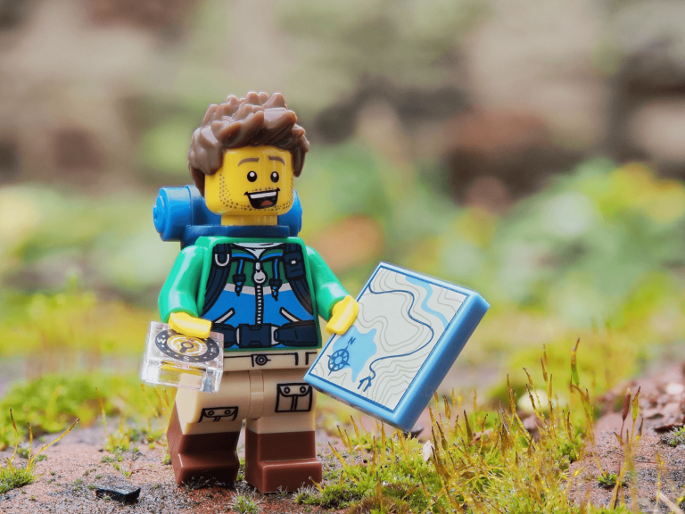 Lego man using a map to depict how to start your graphic design business
