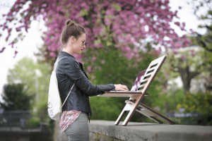 Freelancer working at a standing desk in nature.