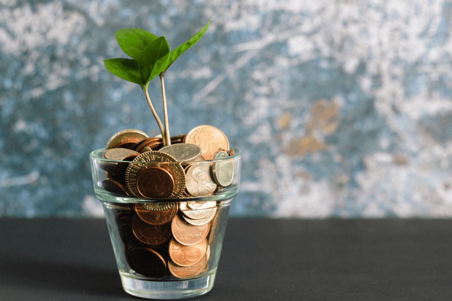 Being a freelancer means setting your rate - a glass full of coins symbolising growth.