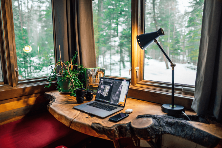 A home office with a desk lamp and natural lighting