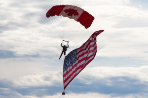 USA and Canadian flags being flown by a skydiver