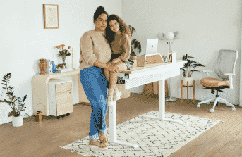 A work-from-home mom with her daughter to show office décor for women.