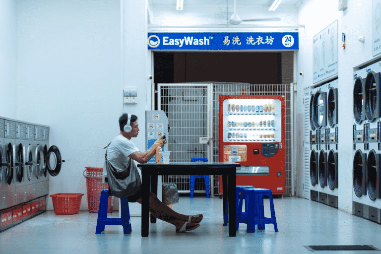 Man listening to a podcast while waiting for his laundry